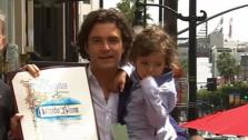 Orlando Bloom holds his and Miranda Kerrs son Flynn at his star ceremony on the Hollywood Walk of Fame. (April 2, 2014)