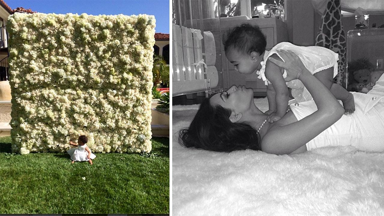 Kim Kardashian and Kanye Wests daughter North West is seen sitting in front of a flower wall he give the reality star for Mothers Day, in this photo Kardashian shared on May 11, 2014. / Kardashian is seen with North in another photo posted that day.