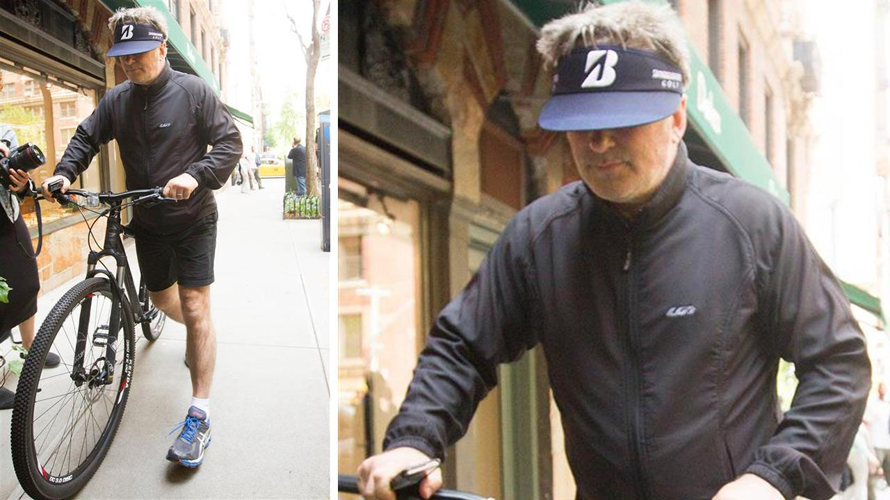 Alec Baldwin rides his bicycle after leaving the NYPDs 13th precinct station. Police say he was detained for riding his bicycle the wrong way and for disorderly conduct.