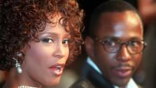 Whitney Houston looks over her shoulder as her husband Bobby Brown looks to her at the premiere of The Wonderful World of Disney movie Cinderella, at Manns Chinese Theater in Hollywood, California on Oct. 13, 1997. - Provided courtesy of AP Photo / Rene Macura, File