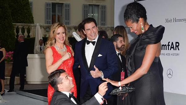 John Travolta and wife Kelly Preston watch producer Oscar Generale propose to his girlfriend, actress and model Denny Mendez, who accepted, at the amfARs 21st Cinema Against AIDS gala at the 67th Cannes Film Festival in France on May 22, 2014. - Provided courtesy of Lionel Hahn / Abaca / Startraksphoto.com