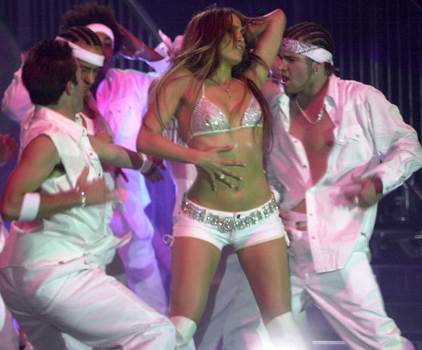 Jennifer Lopez, with the accompaniment of an all-male dance ensemble, performs during the 13th annual White Party, which attracted more than 10,000 gay men to Palm Springs, California on March 31, 2002.