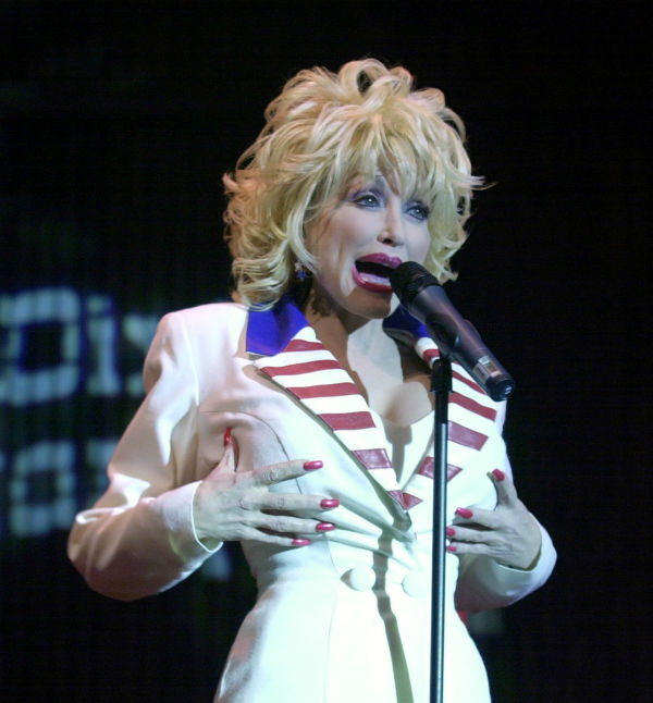 Dolly Parton talks during a news conference for the opening of the Dixie Stampede attraction in Orlando, Fla., Wednesday, June 18, 2003. Parton wore red, white and blue, like an U.S. flag, to publicize her Dixie Stampede in Orlando. Parton said: &#39;I hope people see the brain underneath the wig and the heart beneath the boobs.&#39;  <span class=meta>(AP Photo &#47; Peter Cosgrove)</span>