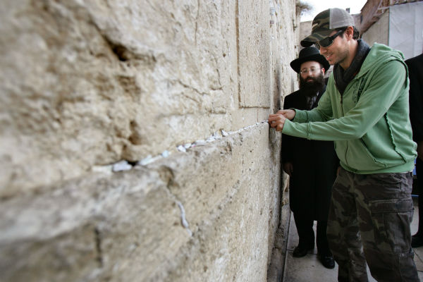 Enrique Iglesias sticks a prayer note into a crack between the stones of the Western Wall during a visit to Jerusalem&#39;s Old City on Dec. 21, 2006. <span class=meta>(AP Photo &#47; Oded Bality)</span>