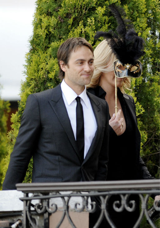 Charlize Theron covers her face with a mask as she arrives with then-boyfriend Stuart Townsend for a party to celebrate the wedding of Salma Hayek and Francois-Henri Pinault in Punta della Dogana, Venice, Italy, on April 24, 2009.