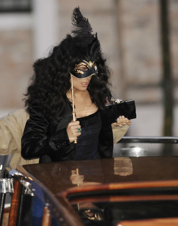 Salma Hayek covers her face with a mask as she...