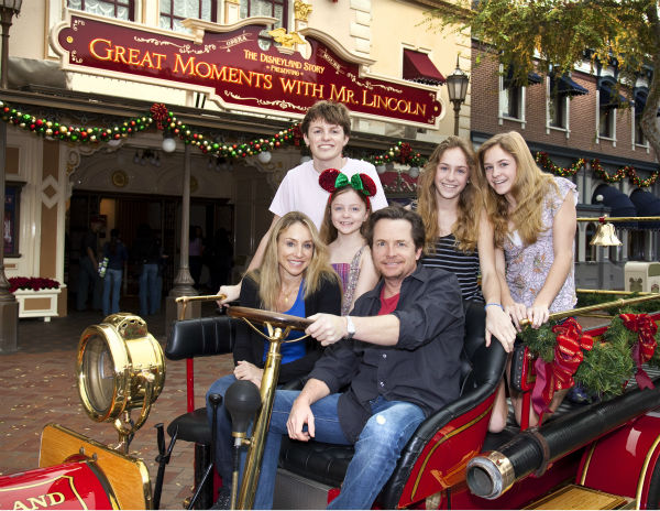 December 21, 2009: Michael J. Fox, wife Tracy Pollan and their children Esme, 8, Schuyler and Aquinnah, 14, and Sam, 20, pose in Walt Disney's antique fire truck outside the newly re-opened 'Great Moments with Mr. Lincoln' attraction at Disneyland in Anah