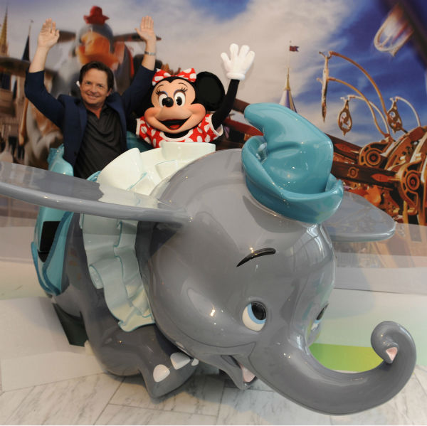 In this publicity image released by Disney, actor Michael J. Fox poses with Minnie Mouse inside a 'Dumbo the Flying Elephant' attraction vehicle at