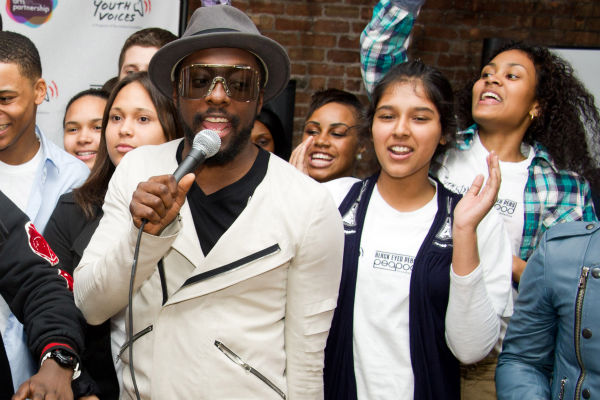 Black Eyed Peas member will.i.am sings with students at the launch of a new Peapod Adobe Youth Voices Academy in New York, Tuesday, April 19, 2011.