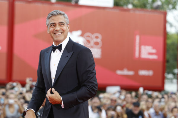 George Clooney poses on the red carpet for the...