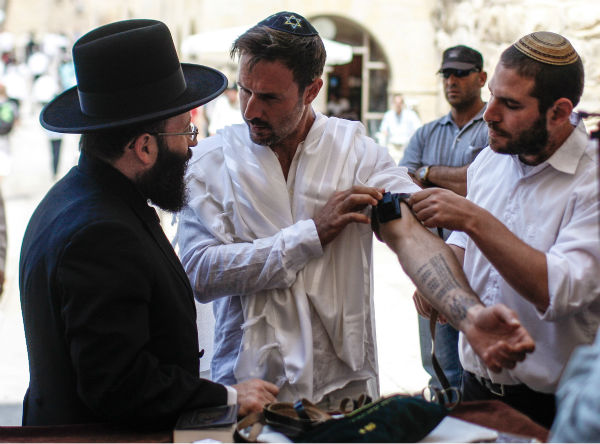 David Arquette, left, celebrates his Bar Mitzvah at the Western Wall in Jerusalem&#39;s Old City on June 11, 2012. The then-40-year-old had visited Israel to shoot a segment for a travel show and ended up having a Bar Mitzvah, a religious rite of passage ceremony given for Jewish boys when they turn 13. The actor tweet: &#39;I had my Bar Mitzvah today at the wall. Finally I&#39;m a man.&#39; <span class=meta>(AP Photo)</span>