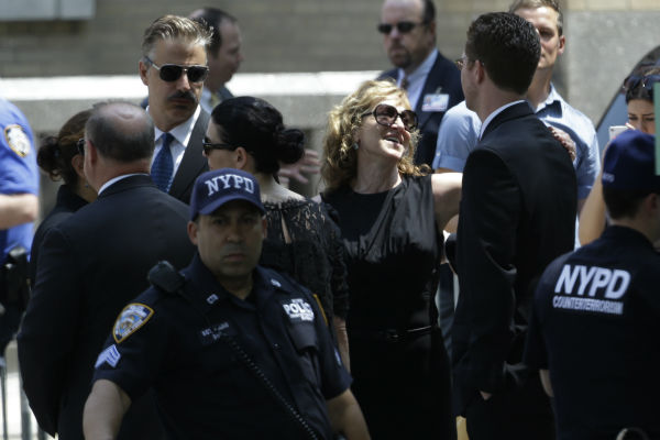 Actress Edie Falco, center, talks to a man outside of the Cathedral Church of Saint John the Divine after the funeral service for James Gandolfini in New York on June 27, 2013. Gandolfini, who played Tony Soprano in the HBO show &#39;The Sopranos,&#39; died at age 51 while vacationing in Italy. Falco played his wife, Carmella, in the series. <span class=meta>(AP Photo &#47; Julio Cortez)</span>