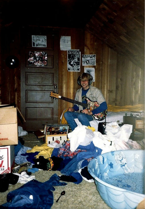 In this undated photo provided by Kim Cobain, sister of Kurt Cobain, a young Kurt plays guitar in his childhood home in Aberdeen, Washington.