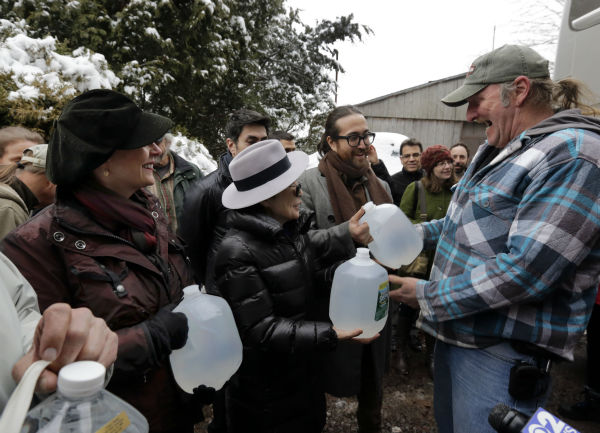 Actress Susan Sarandon, left, Yoko Ono, second left, and her son Sean Lennon, present bottles of clean drinking water to Ray Kemble  in Dimock, Pennsylvania during a tour of natural gas drilling sites on Jan. 17, 2013. <span class=meta>(AP Photo &#47; Richard Drew)</span>
