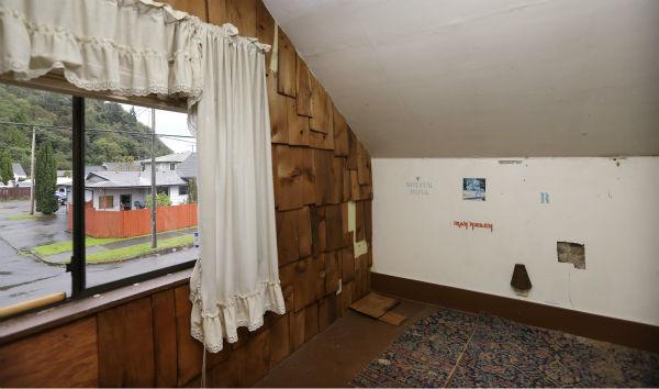 In this photo taken on Sept. 23, 2013, an attic bedroom used by Kurt Cobain still has the stencil-like logos of bands that he reportedly put on the walls, as well as the holes he put in them, at his childhood home in Aberdeen, Washington.