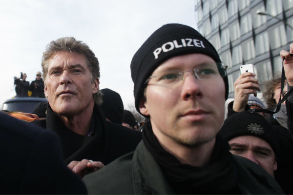 David Hasselhoff, left, is accompanied by police as he attends a protest against the removal of a section of the East Side Gallery, a historic part of former Berlin Wall, in Berlin on Sunday, March 17, 2013. Hasselhoff is fondly remembered by many Germans for releasing a song called &#39;Looking for Freedom&#39; shortly before the fall of the Wall in 1989. <span class=meta>(AP Photo &#47; Markus Schreiber)</span>