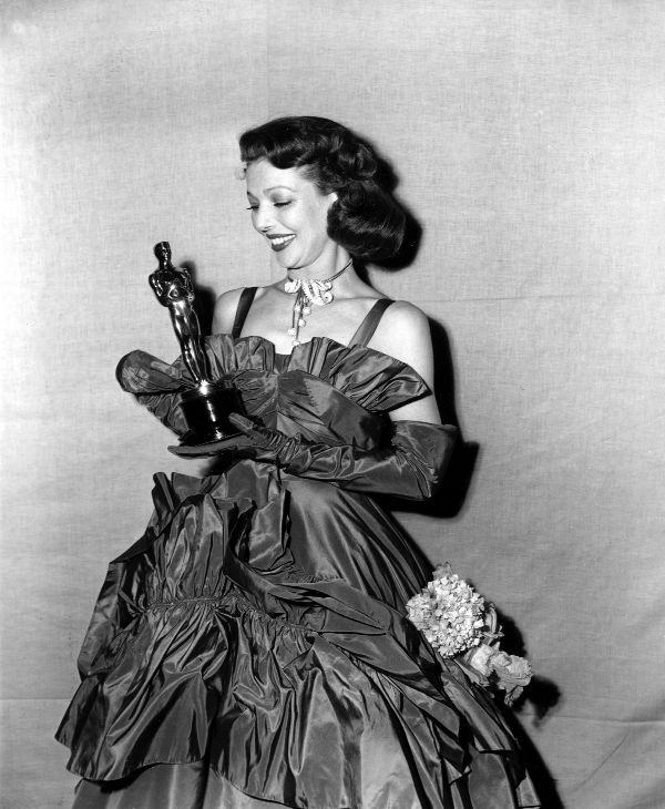 Loretta Young looks at her Oscar at the 1947 Academy Awards held at the Shrine Civic Auditorium in Los Angeles, California on March 20, 1948. Young was named best actress for her role in &#39;The Farmer&#39;s Daughter.&#39; <span class=meta>(AP Photo)</span>