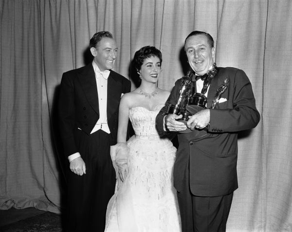 Walt Disney displays four Oscars he won at 26th annual Academy Awards to actress Elizabeth Taylor and her husband, Michael Wilding  in Los Angeles on March 25, 1954. <span class=meta>(AP Photo)</span>