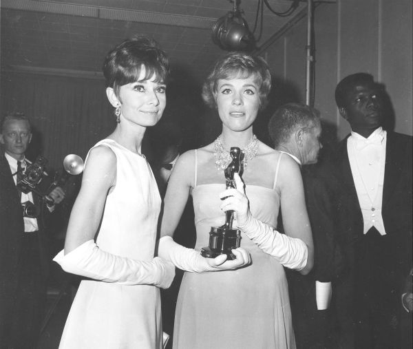 Julie Andrews, holding her Oscar statuette, poses with Audrey Hepburn backstage at the 37th annual Academy Awards ceremony at the Santa Monica Civic Auditorium in Santa Monica, California on April 5, 1965.  Andrews won for her role as Mary Poppins in &#39;Mary Poppins.&#39; Standing at far right is actor Sidney Poitier. <span class=meta>(AP Photo)</span>