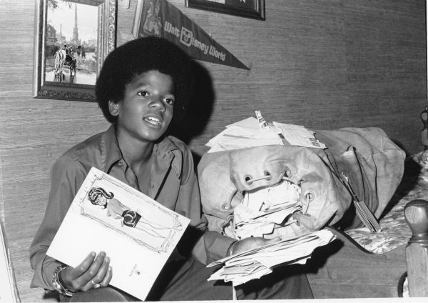 "<div class=""meta ""><span class=""caption-text "">Michael Jackson, who at 13 in this photo and a member of the Jackson Five, holds cards and letters sent by fans, while sitting in a room in his family's home in Encino, California in 1972. (AP Photo)</span></div>"