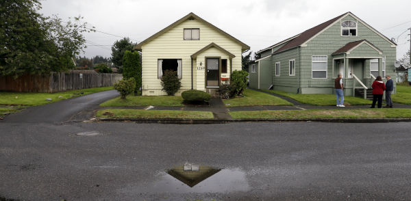 This  Sept. 23, 2013 photo shows the childhood home of Kurt Cobain, the late frontman of Nirvana, left, along an alley in Aberdeen, Washington.