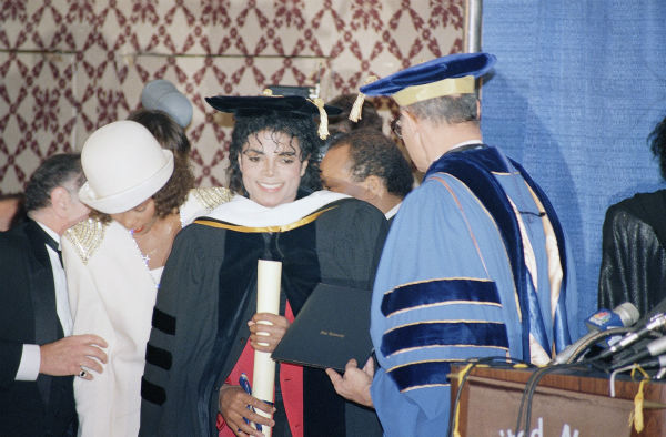 "<div class=""meta ""><span class=""caption-text "">Whitney Houston talks with an unidentified man (at left rear) as Michael Jackson receives an honorary degree from Fisk University in June 1980. The degree was presented by the college's president, Dr. Henry Ponder. (AP Photo)</span></div>"
