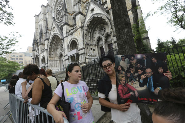 Stephanie Solano, right, and her daughter Sophia wait in line outside Cathedral Church of Saint John the Divine ahead of the funeral service of James Gandolfini in New York on June 27, 2013. Gandolfini, who played Tony Soprano in the HBO show &#39;The Sopranos,&#39; died at age 51 while vacationing in Italy.  <span class=meta>(AP Photo &#47; Mary Altaffer)</span>