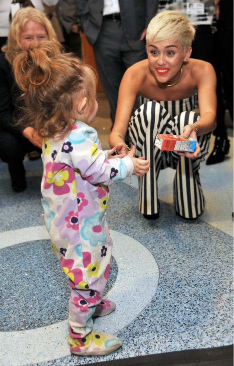 Miley Cyrus plays with patient Janessa Martinez,...