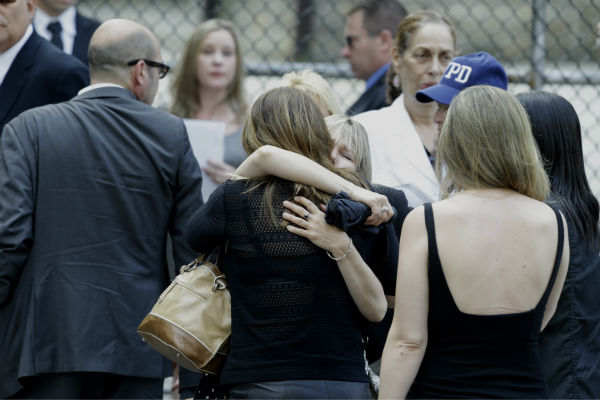 Women embrace outside of Cathedral Church of Saint John the Divine before the funeral service of James Gandolfini in New York on June 27, 2013. Gandolfini, who played Tony Soprano in the HBO show &#39;The Sopranos,&#39; died at age 51 while vacationing in Italy. <span class=meta>(AP Photo &#47; Julio Cortez)</span>