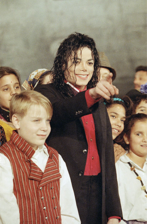 Michael Jackson stands with members of a children&#39;s choir during ceremonies at New York&#39;s John F. Kennedy International Airport on Tuesday, Nov. 24, 1992 to mark the shipment of 93,700 pounds of relief supplies destined for strife-torn Sarajevo. The shipment was joint effort of AmeriCares and Jackson?s Heal the World Foundation. <span class=meta>(AP Photo &#47; Michael Albans)</span>