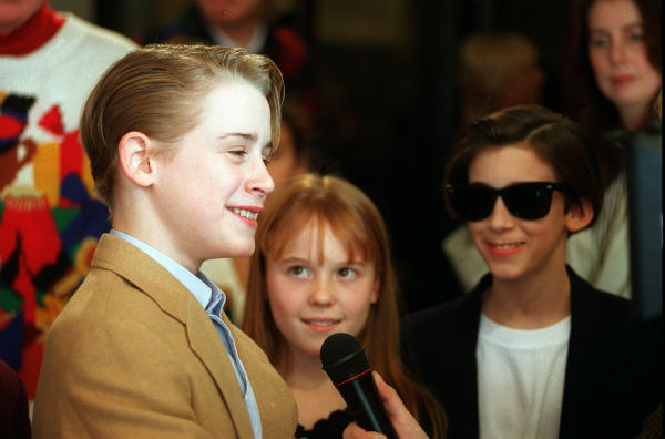 Macaulay Culkin, left, speaks to the media before the premiere of 'Richie Rich' at the Mann's Bruin Theater in Los Angeles, California on Saturday, Dec. 17, 1994.  Looking on are co-stars Stephi Lineburg, center, and Michael Maccarone.