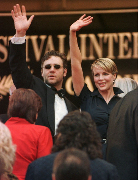 Kim Basinger, right, and Australian actor Russell Crowe waves to fans as they arrive for the screening of Curtis Hanson's film 'L.A Confidential,' in competition for the Cannes Film Festival on May 14, 1997.