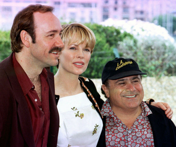 Kim Basinger poses between Kevin Spacey, left, and Danny De Vito during the presentation of 'L.A. Confidential,' in competition for the Cannes,France, Film Festival on May 14, 1997.