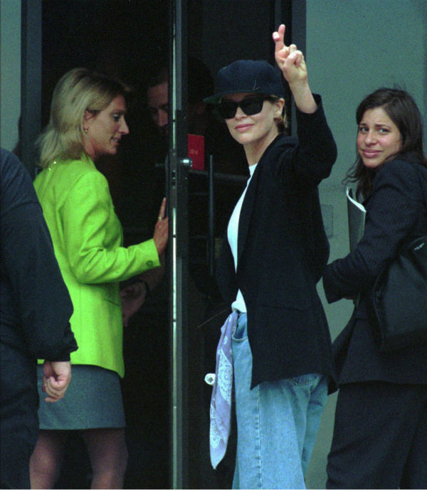 Kim Basinger, center, raises crossed fingers as she enters Huntingdon Life Sciences in East Millstone, N.J. on July 3, 1997.