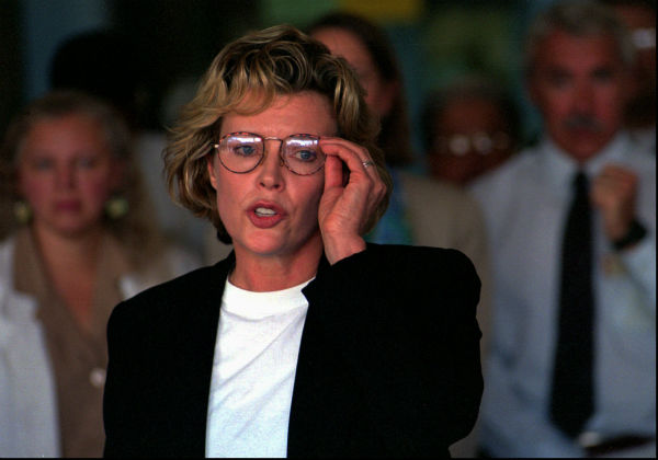 Kim Basinger adjusts her glasses as she reads a prepared statement at the Rio Grande Zoo in Albuquerque, N.M. on Aug. 26, 1997.