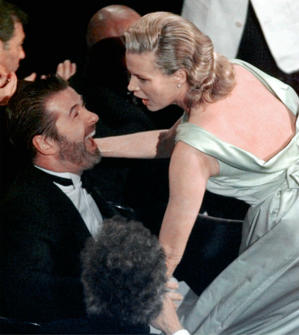 Kim Basinger reaches for her husband, Alec Baldwin, after she won Best Supporting Actress for her role in 'L.A. Confidential' at the Academy Awards in Los Angeles on March 23, 1998.