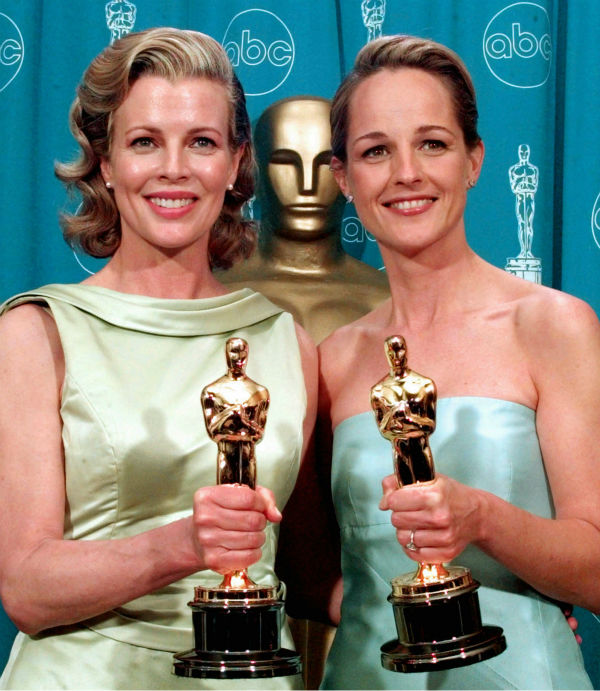 Kim Basinger, left, shows off her Oscar for Best Supporting Actress with Helen Hunt, right, and her Oscar for Best Actress at the 70th Academy Awards in Los Angeles on March 23, 199