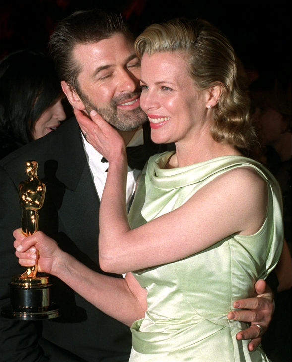 Holding her Oscar, Kim Basinger gives husband Alec Baldwin an affectionate touch before photographers outside a post Academy Awards party at Morton's restaurant in West Hollywood, California on March 24, 1998.  Basinger won the Oscar for Best Supporting