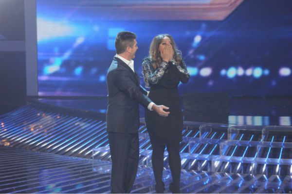 Co-judge Simon Cowell (L) reacts as Melanie Amaro (R), the contestant he mentored, is announed the winner of season 1 of the FOX show 'The X Factor' on Dec. 22, 2011.