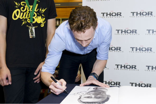 Tom Hiddleston signs a sketch of himself at a &#39;Thor: The Dark World&#39; fan event in Sydney, Australia on Oct. 9, 2013. He reprises his role as Loki in the Marvel film. <span class=meta>(Esteban La Tessa - La Tessa Photography)</span>