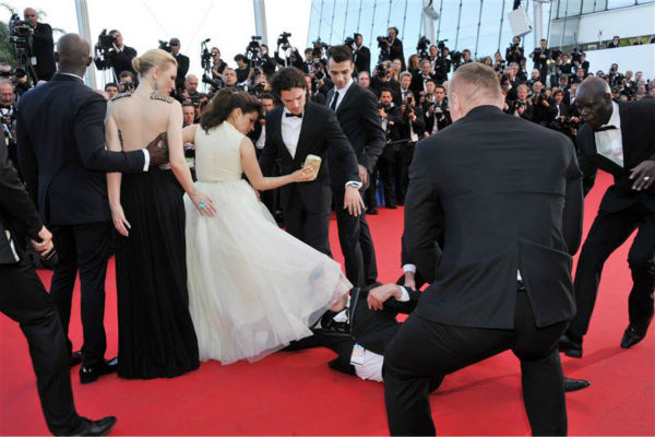 Security officials try to restrain notorious prankster of celebrities, Ukrainian reporter Vitalii Sediuk, after he crawled under actress America Ferrera&#39;s ball gown at a screening of &#39;How To Train Your Dragon 2&#39; at the 2014 Cannes Film Festival on Friday, May 16, 2014. Also pictured: Kit Harington and Cate Blanchett. <span class=meta>(Camilla Morandi &#47; IPA &#47; Startraksphoto.com)</span>
