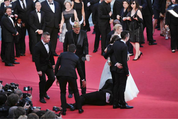 Security officials try to restrain notorious prankster of celebrities, Ukrainian reporter Vitalii Sediuk, after he crawled under actress America Ferrera&#39;s ball gown at a screening of &#39;How To Train Your Dragon 2&#39; at the 2014 Cannes Film Festival on Friday, May 16, 2014. Also pictured: Cate Blanchett. <span class=meta>(Aurore Marechal &#47; ABACA &#47; Startraksphoto.com)</span>