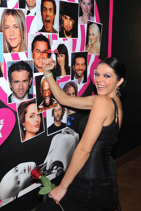 Adrianne Curry points a dart at a photo of the head of her ex, 'Brady Bunch' star Christopher Knight, on SVEDKA's famous ex dart board, at SVEDKA Vodka's Anti-Valentine's Day Bash at AGENCY Boutique Nightclub in Los Angeles on Jan. 31, 2012.