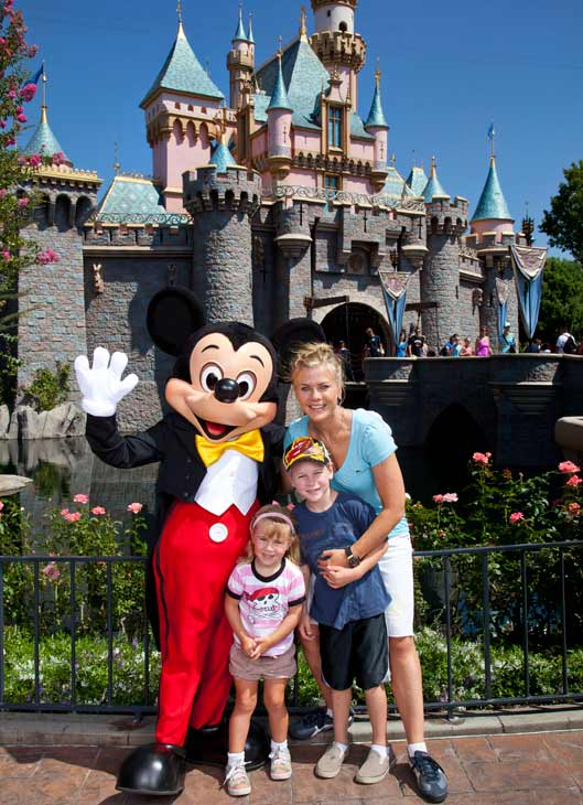 'Days of Our Lives' star and 'The Biggest Loser' host Alison Sweeney and her children Benjamin, 7, and Megan, 3, pose with Mickey Mouse outside Sleeping Beauty's castle at Disneyland park in Anaheim, California, on Friday, Aug. 31, 2012.