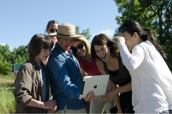 "<div class=""meta ""><span class=""caption-text "">Chandler Riggs (Carol Grimes), Director Guy Ferland, Co-Executive Producer Denise Huth and Lauren Cohan (Maggie Greene) watch something on an iPad on the set of AMC's 'The Walking Dead' while filming episode 2 of season 4, titled 'Infected,' which aired on Oct. 20, 2013.  (Gene Page / AMC)</span></div>"