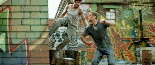 "<div class=""meta ""><span class=""caption-text "">David Belle and Paul Walker appear in a scene from the 2014 action movie 'Brick Mansions.' Walker plays an undercover cop. The film is set in Detroit in 2018. Brick Mansions is a government-quarantined housing project that is home to criminals. Belle plays one of its residents, Lino. The actor also starred in the French film 'District B13,' on which 'Brick Mansions' is based. (Philippe Bosse / Relativity Media / EuropaCorp /Transfilm International Inc.)</span></div>"