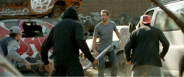Paul Walker appears in a scene from the 2014 action movie &#39;Brick Mansions.&#39; He plays an undercover cop. The film is set in Detroit in 2018. Brick Mansions is a government-quarantined housing project that is home to criminals. <span class=meta>(Philippe Bosse &#47; Relativity Media &#47; EuropaCorp &#47;Transfilm International Inc.)</span>