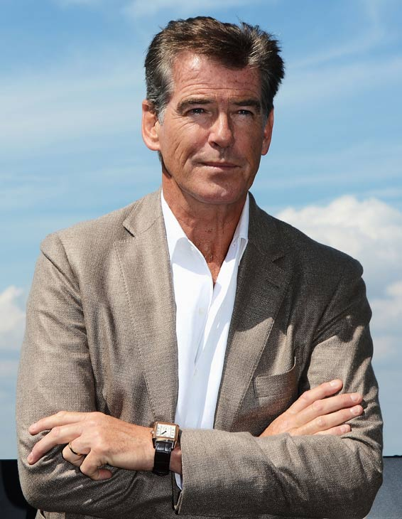 Pierce Brosnan, wearing a suit and a Squadra Rose Gold Jaeger-LeCoultre watch, appears a