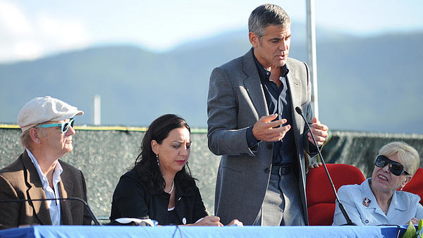 Clooney appears in a photo speaking to residents...