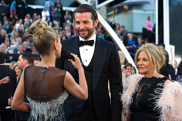 ABC guest host and Broadway and TV star Kristin Chenoweth and Bradley Cooper, Oscar-nominee for Actor in a Leading Role arrive for The Oscars at the Dolby Theatre in Hollywood, California on Feb. 24, 2013. Also pictured: Cooper's mother, Gloria.